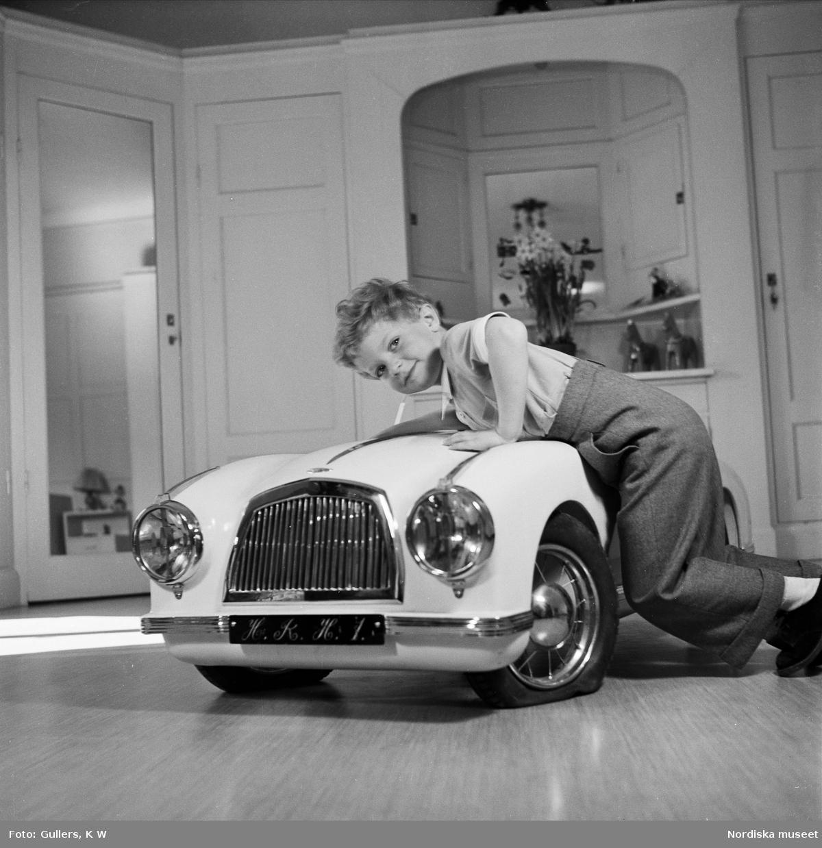 "Kronprins Carl Gustaf leker med en trampbil. På nummerplåten ""H.K.H.1."""