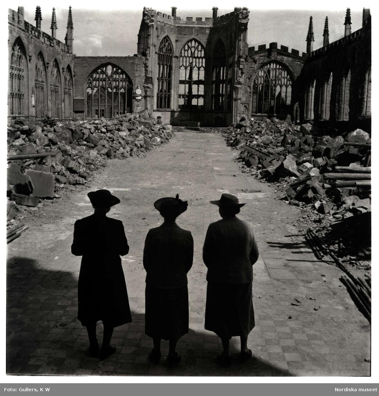 Tre kvinnor vid ruinerna av den sönderbombade katedralen i Coventry