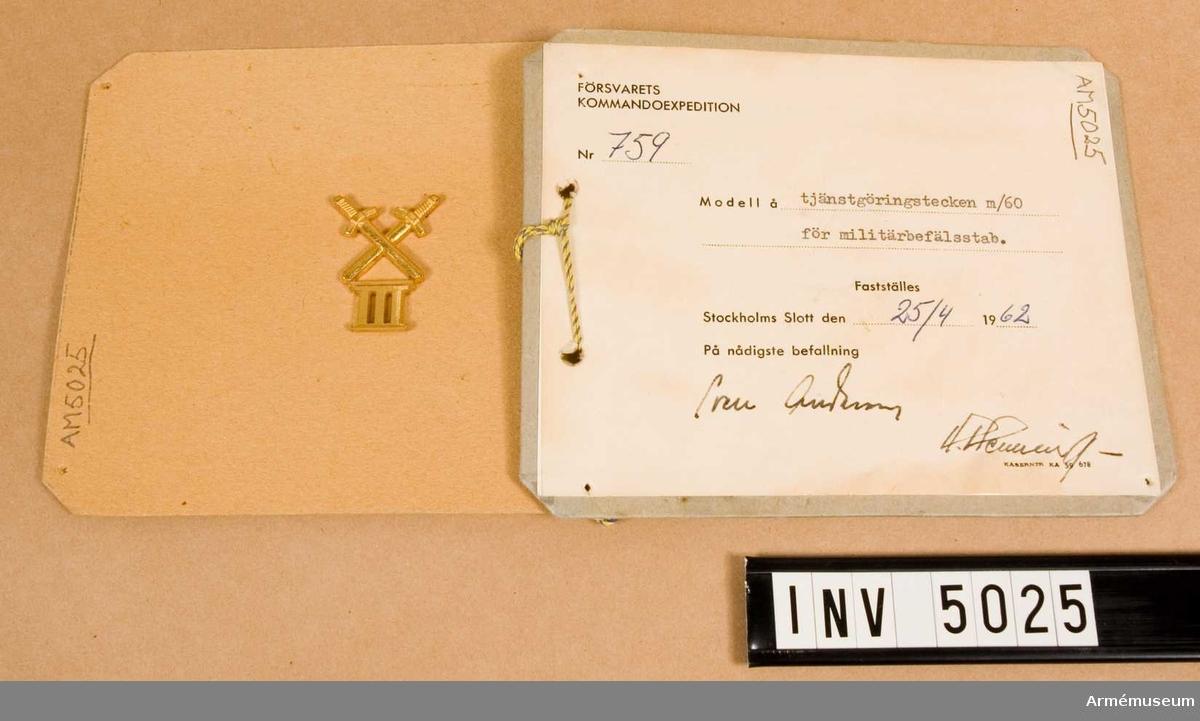 Tillverkat i metall och alltid i metallfärg m/1960 guld. Utgöres av två korslagda svärd mellan vars spetsar vederbörligt militärområde anges med romerska siffror.