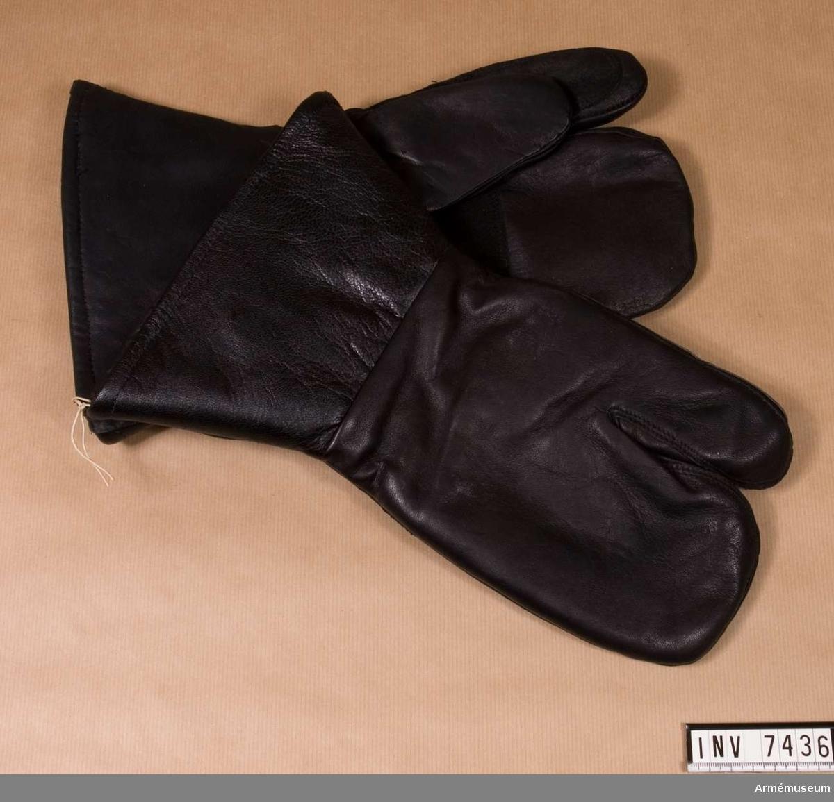 Handskar fm/1947, motor-. 1 par. Svarta skinnhandskar med tumme och pekfinger fria. Handflata, tumme och pekfinger är skinnskodda med den råa sidan ut av det  svarta skinnet. Fodrade med vitt fårskinn. Vänster handske har en etikett med text: ÖSB 2 Industrier. Storlek 2.