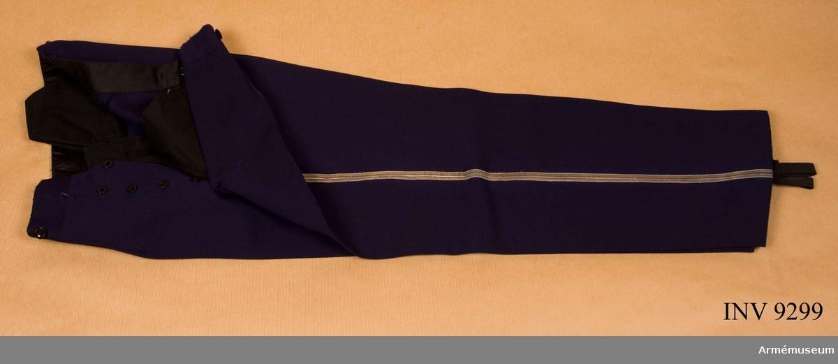 I kläde av samma mellanblå färg som vapenrocken med 12 mm bred silvergalon längs med yttersömmen. Jylfknäppning och i linningen knappar för hängslen. Knapparna är märkta Lindahl Linköping. Gåva av direktör Jean Ramstedt i Stockholm.