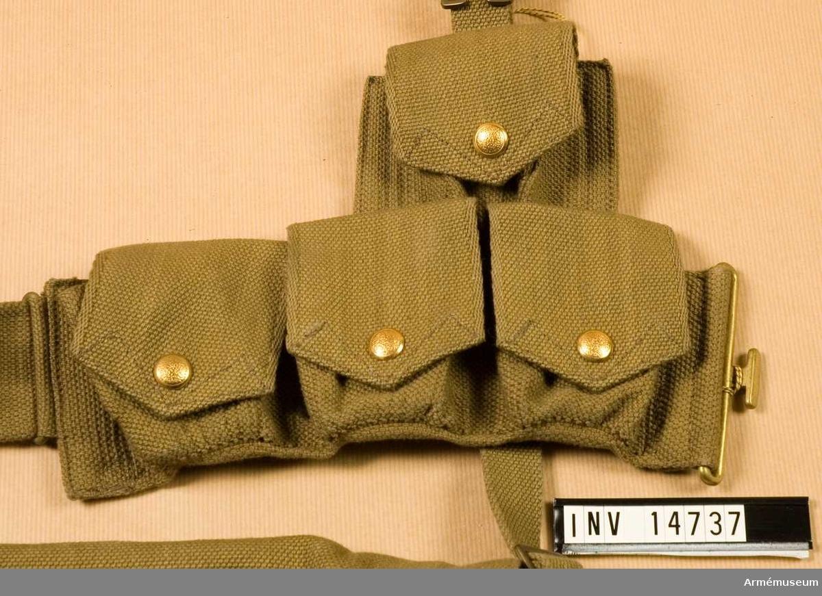 """Grupp C. Alla persedlar är gjorda av thockt khakityg (eng. wibbing) och alla metalldelar (knappar, spännen, ringar och krokar) är av mässing.En av två patronväskor med vardera fyra """"fickor"""". Den ena bäres  på livremmens vänstra sida, den andra på höger. Väskorna stänges med knappar.  De är grupperade i två rader: i den övre raden en väska och i  den nedre tre. Båda raderna är sammansydda och bäres på vänstra  och högra sidan av livremmen.  I patronväskorna finns två mellanväggar.  På insidan av väsklocken (i övre raden) finns en stämpel: """"M.E.Co.1913"""". LITT  Arméen Album II. Die Englische Armée und Marine. Uniformen  im Kriege. Verlag von M. Ruhl, Leipzig. Sida 13. """"Lederzeug"""":  Manskapets fältutrustning är gjord av khakifärgat """"Gurtband"""" (på  eng. Wibbing). Bilaga - bilder: engelska soldater med ammuni- tionsgördel av samma tyg. Enligt kapten W. Granberg."""