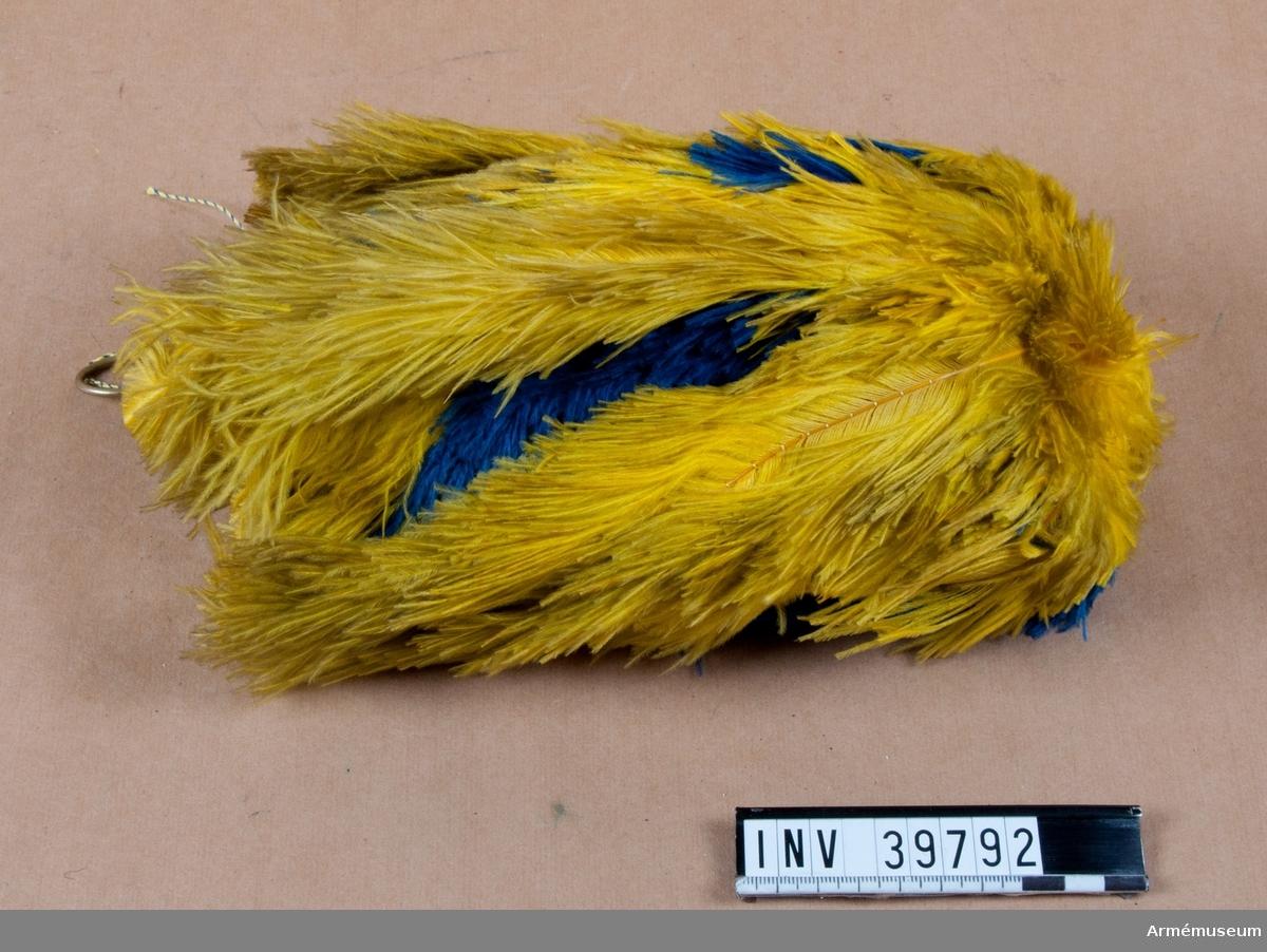 Grupp C I. Hängande plym till trekantig hatt m/1854-59. Ur paraduniform för artilleristabsofficer vid Göta artillerireg. Fastställd modell 1872. Består av attila, hatt, plym, långbyxor, stövlar, sporrar, ägiljett, knutskärp, sabelkoppel, kartusch med rem, handskar. RSO.