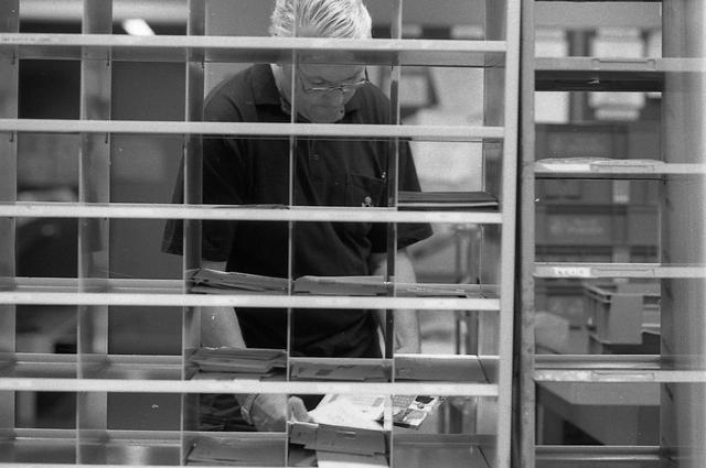 En posttjänsteman sorterar post inne i sorteringsdelen på en postanstalt. Tillhör en dokumentation av en lantbrevbärare i trakten av Valdermarsvik av fotograf Ove Kaneberg.