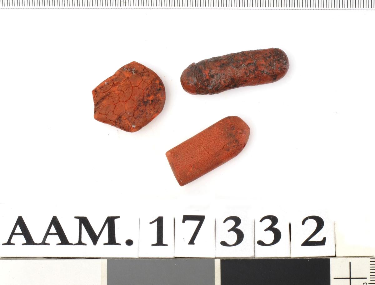 Lakkstang, rød  fra skrinet med signetene.  I tre deler. I bit sort lakkstang.   a) Det største stykket.  L 4,1 .  B 1,9.  Litt flat  med ovalt tverrsnitt   b) Et stykke rød lakkstang.  L 3,5. B. 1,5. Ovalt tverrsnitt. (G 1348).    c) Bredere, flatere stykke.  L. 2,7. B. g 2,6. Rundet i forkant, avslått i spiss.    d) Et sort stk. lakkstang  av samme form som b). L. 2,9. B. 1,8.