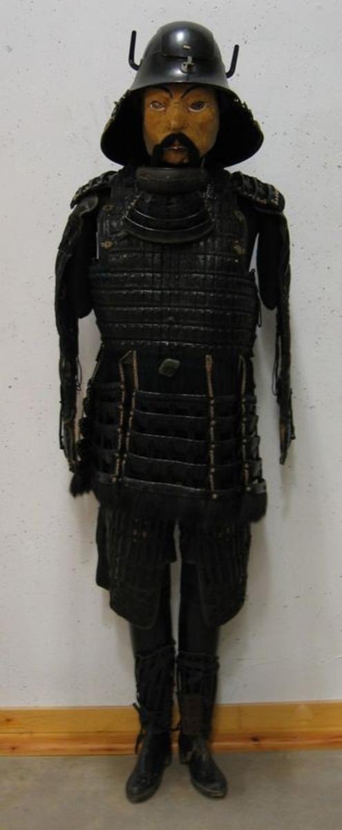 01367: Lamellutrustning en s.k. ''Yoroi'' med hjälm ''Kaouto''.  Förutom ihopvävda rektangulära metallplattor (längs med dräktens armar och ben), textil samt tagel består dräkten troligen av läderplattor (på dräktens fram- och baksida samt på axlarna) som lackerats. För att få till en så hård yta kan lädret ha genomgått en process kallad Cuir bouilli där lädret kokats i vatten, ibland med tillsats av vax eller olja. Masken av papper är tillverkad vid ett senare tillfälle.