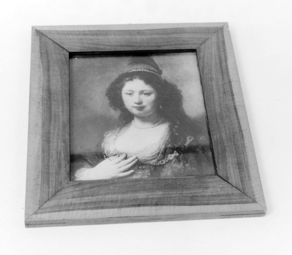 Rektangulær bjerkefinerramme med  Kvinne; brystbilde, kropp noe venstrev., v. hånd på  brystet, løst, mørkt hår m. perler og fjær; stor kjoleutrigning.