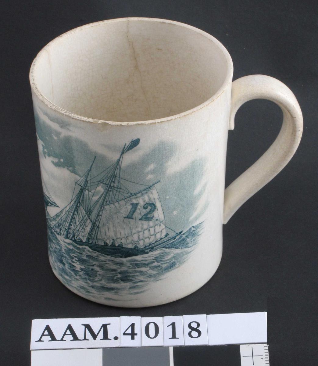 I blågrønn  glasur  et sjøstykke med en dampbåt tv. og en seilskute th. med det  amerikanske flagg og merket 12 på seilene.