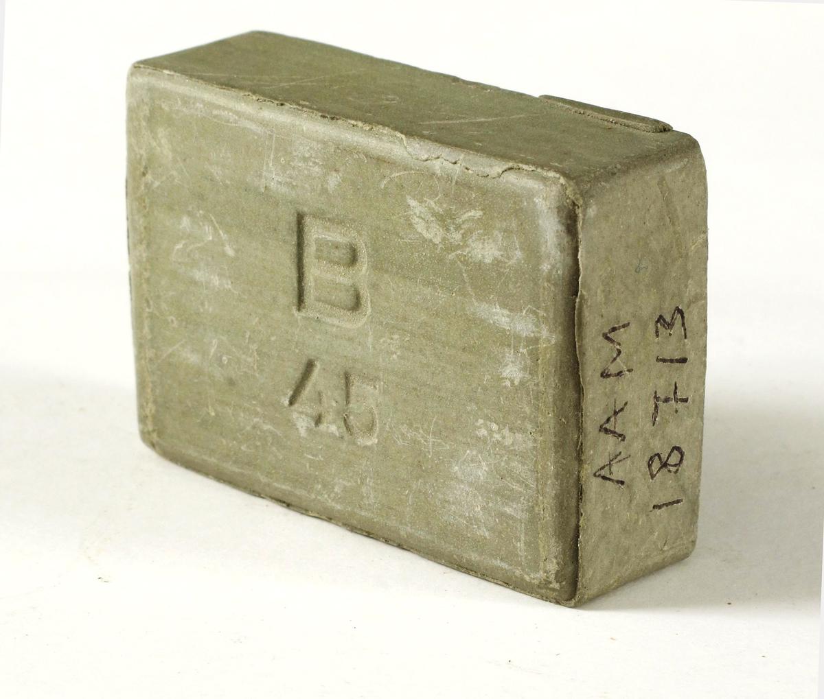 B-såpe,   fra krigen 1940-45 (siste del).  Grågrønn   finkornet  sepe, merket   B 45.   Rette sider,   rektangulær.    Tilstand: ubrukt.