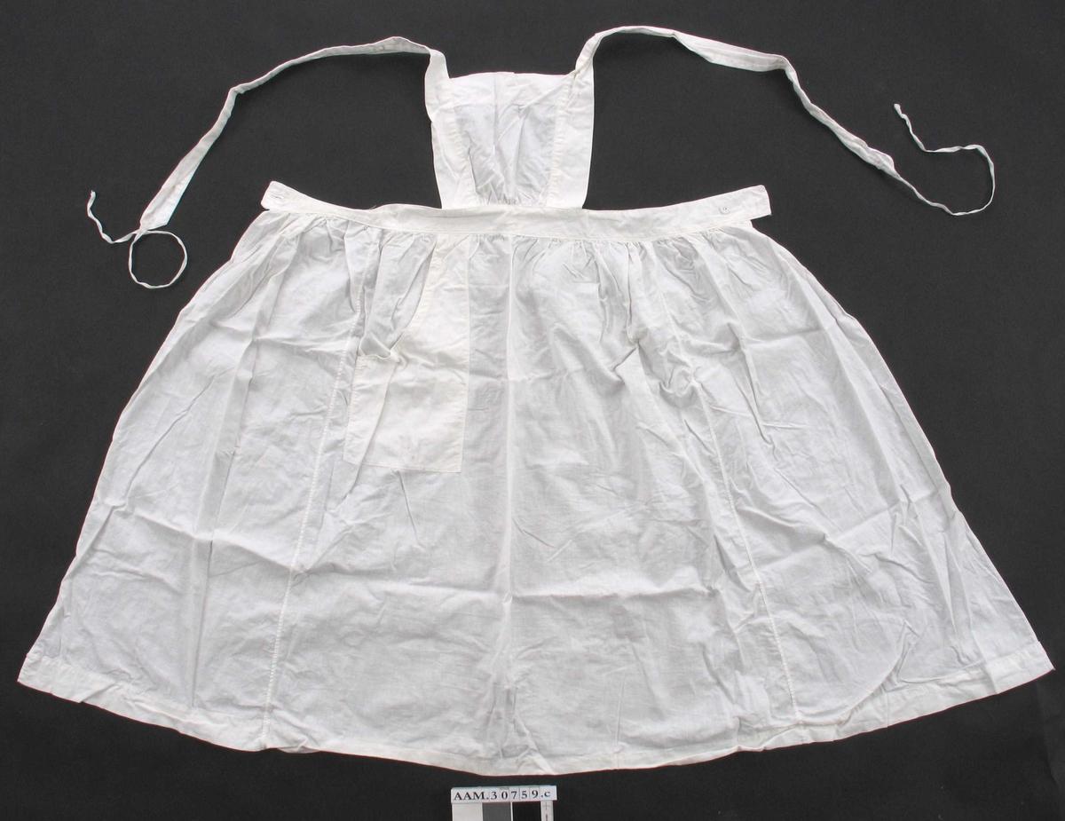 Form: 3 høyder rynket til linning, lomme ved den ene hoften. Smekke, seler med knapphull og bendelbånd i enden.