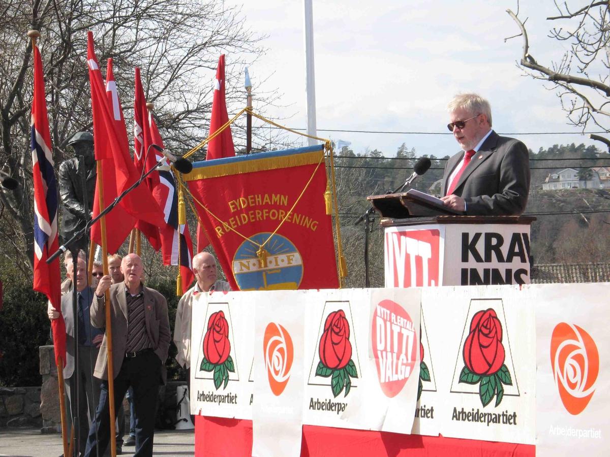 1.mai på Eydehavn. Talerstolen pyntet med rød rose motiv, med flaggborg og fane i bakgrunnen t.v. Dagens hovedtaler.