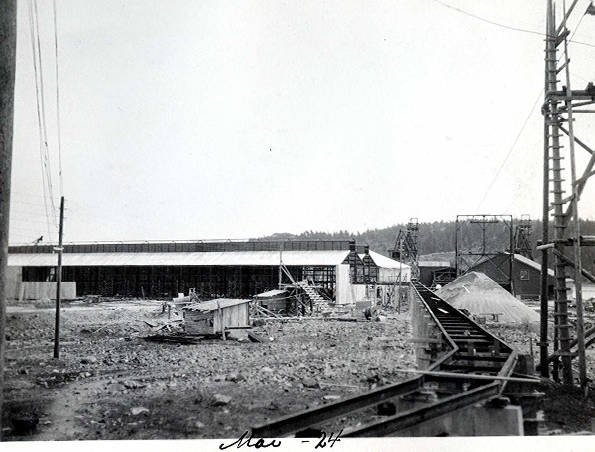 """""""07/05-1924"""" Nitriden. Bygning for steking av elektrodekull. Skinnegangen, """"høybanen"""", går ut til, inn i og sør for, stekeribygningen. Taubanemast til høyre. Tromøy i bakgrunnen."""
