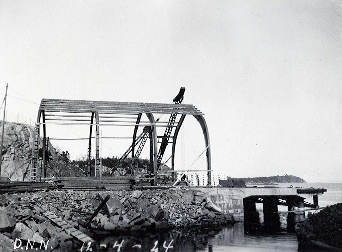 """""""12/04-1924"""" Nitriden. Østre kai. Stålkonstruksjoner for lagerbygning. Kran i bakgrunnen. Tromøysund og Hvideberget i bakgrunnen."""