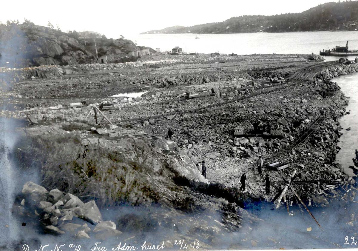 """""""20/02-1912"""" Nitriden. Planering av fabrikktomten ut mot kaianlegget. Tomøysund og Tromøy til høyre. Dampskip ved """"kai""""."""