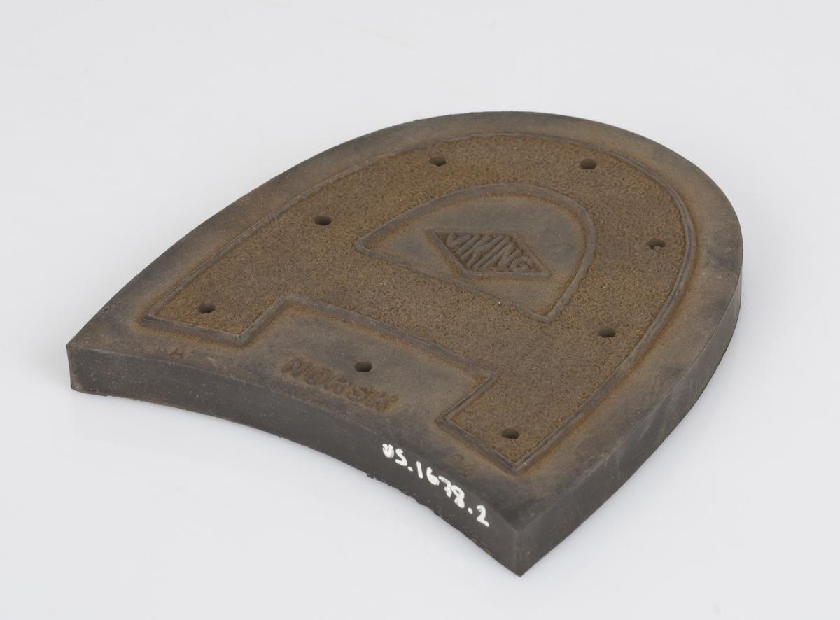 Hælflekk av plast. Mønster og logo på undersiden av hælflekken.