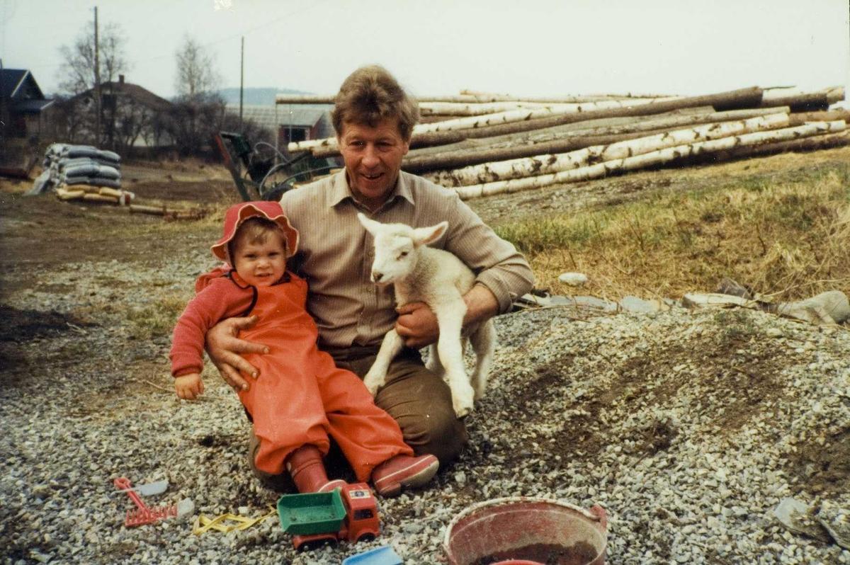 Far med barn og et lam.