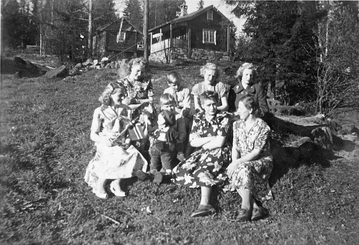 Familie. 6 kvinner og 3 barn på 17. mai 1951. Tutlidalen, Gullverket. Foran fra v.: Reidun Andersen, Arne Martinsen med Rune Andersen på fanget, Margrete Martinsen (gift Sveen), Ragnhild Martinsen. Bak fra v.: Bjørg Martinsen (gift Millidal), Reidar Martinsen, Solveig Storbråten, Evy Storbråten.