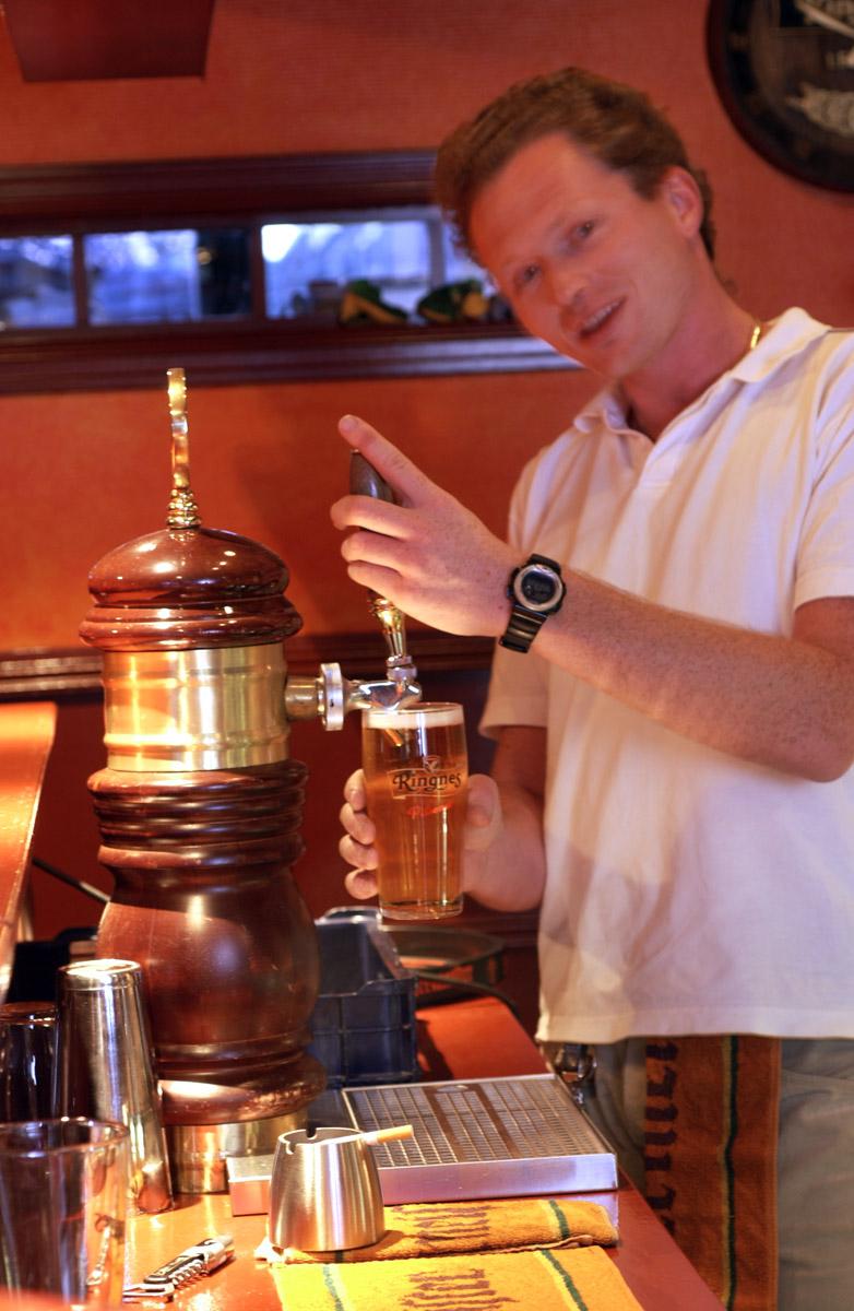 Bartender med sigarett ved tappekran. Sveaborg Bar & Spisested ved bardisken