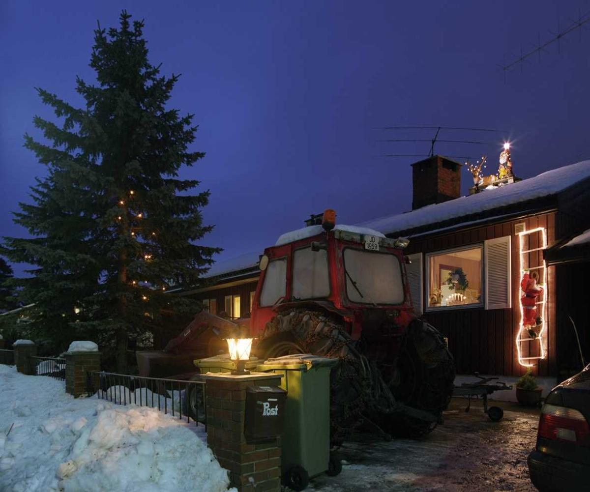 Julebelysning  Reinsdyr med lyslenke og nisse med lysende lykt på taket. Nisse som kravler opp veggen på lysstige og lyslenke i gran ved enebolig.