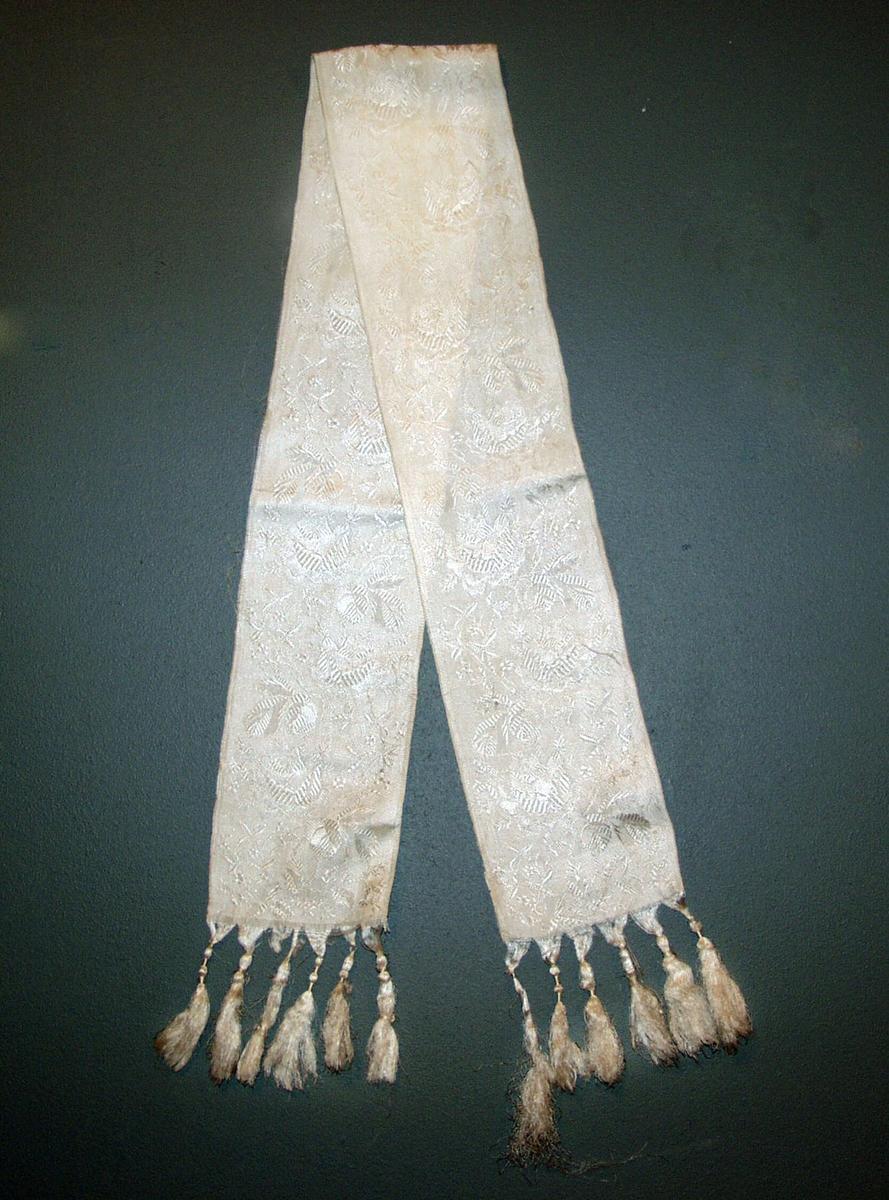 Form: Smalt sjerf, frynsekant 8 cm med snurr. Damaskvevet silke.