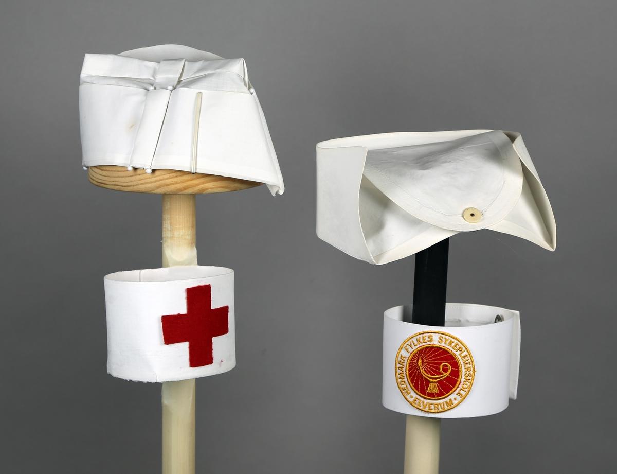 2 stk. hetter til sykepleieuniform.  Røde Kors og Hedmark sykepleieskole.  2 stk. armbind til sykepleieuniform. Røde Kors og Hedmark sykepleieskole.   Hettene er brettet av et glatt stoffstykke. Satt sammen med søsternåler, stivet og brettet.