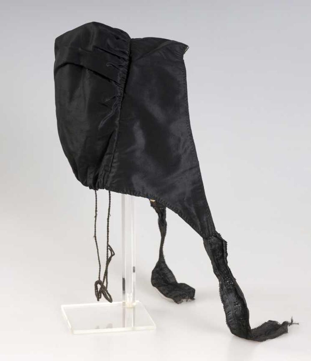 Rynkelue i svart silketaft, med svarte mønstervevde silkeband til knyting.