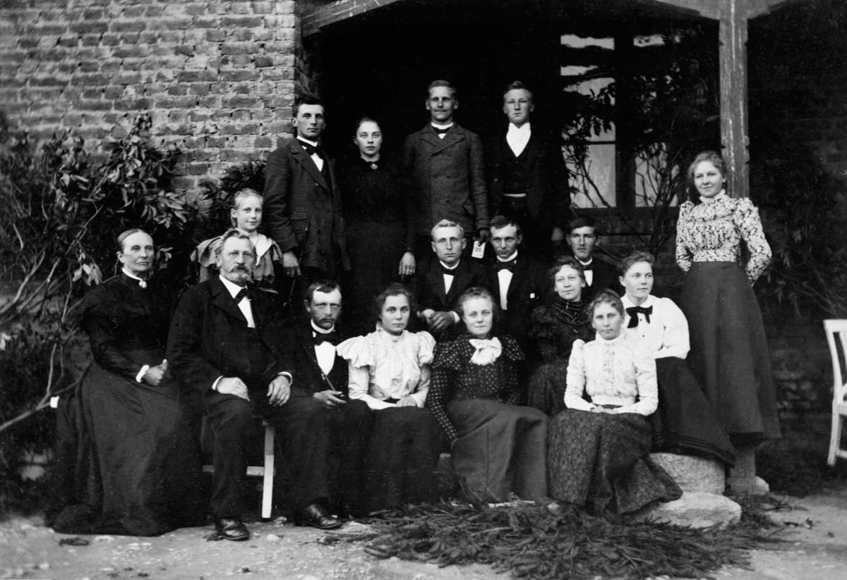 Familien Mengshoel samlet på verandaen på hovedbygningen, Mengshoel, Nes, Hedmark. Øverst fra høyre er agronom Ole Jensen Mengshoel (1873-1962), Marthe Andreasdatter Heramb (1873-1948), Even Jensen Mengshoel (1870-1913). Andre rad fra høyre er Louise Sendstad (1881-1955),  agronom Aarstrand, Børre Mølstad, Simen Borud Baldishol, Jens J. Mengshoel. Tredje rad fra høyre er Marie Fossum, Helga Mengshoel (1878-1963), Amalie Mengshoel (1875-1957), Karen Mølstad, Petra Mølstad, Even Berntsen Skinstad (1866-1935), Jens Evensen Mengshoel (1838-1919), Lise Olsdatter Baldishoel (1841-1927).