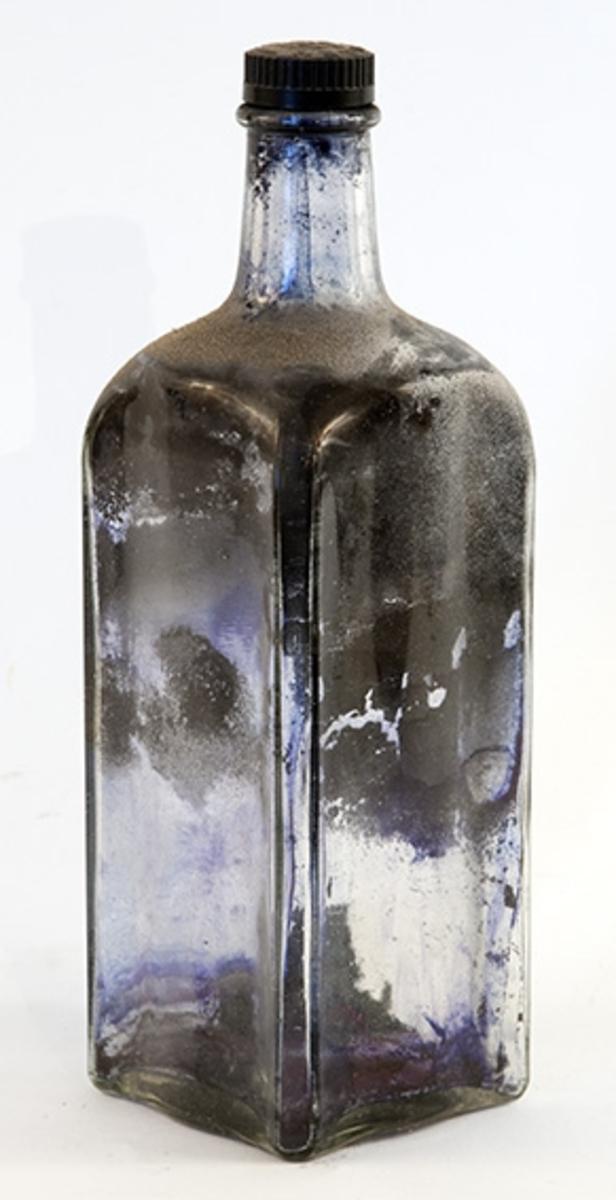 Kvadratisk flaske med sort skrukork. Har inneholdt blekk.